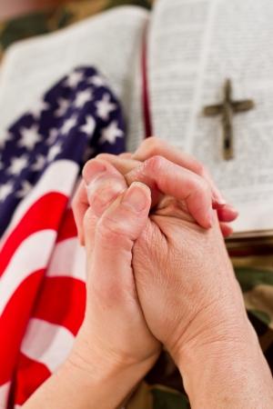 viernes santo: manos femeninas en la oraci�n con una Biblia abierta, una bandera estadounidense y un uniforme de camuflaje en el fondo