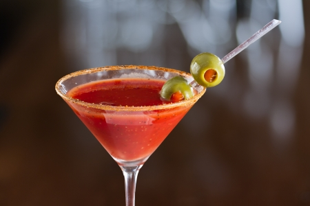 closeup of a bloody mary cocktail garnished with olives isolated on a busy bar top