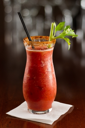 close-up van een Bloody Mary cocktail gegarneerd met een selderij zieke die op een drukke bar boven