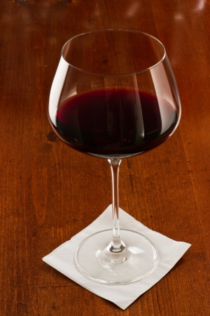 long stem wine glass with red wine served on a bar top