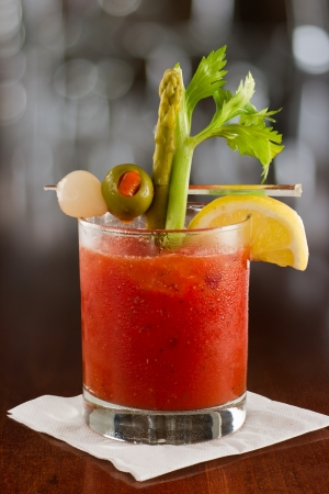 bloody mary cocktail isolated on a busy bar top garnished with onions, olives, asparagus and celery Imagens