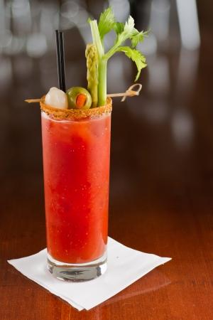Bloody Mary cocktail geïsoleerd op een drukke bar boven gegarneerd met ui, olijven, asperges en selderij Stockfoto