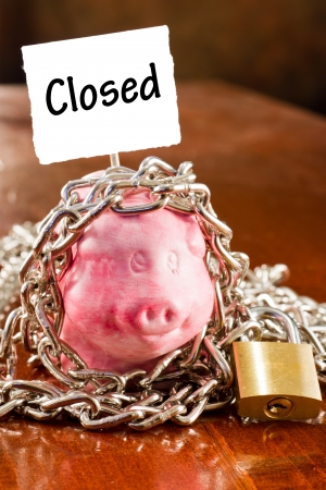 locked: concept of a bad economy  piggy bank with lock and chain Stock Photo