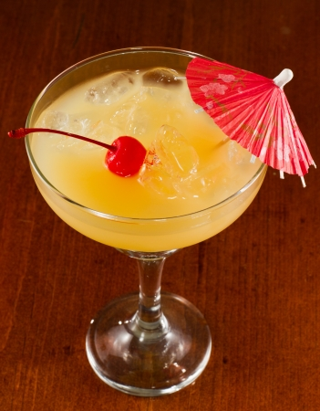 tropical drink on a bar top garnished with a red parasol photo