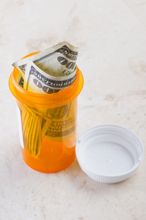vile: empty medicine vile with american cash representing the cost of free healthcare