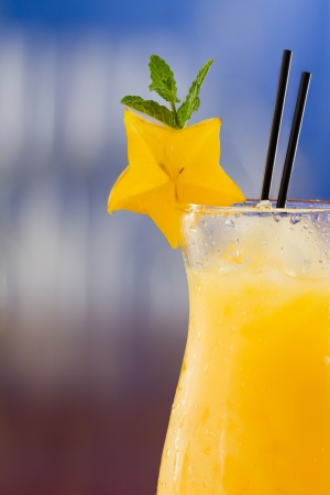 fresh tropical juices mixed and served in a glass decorated with a carambola slice and fresh mint photo