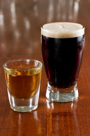 shot: close up of a dark beer and a shot on a busy bar top