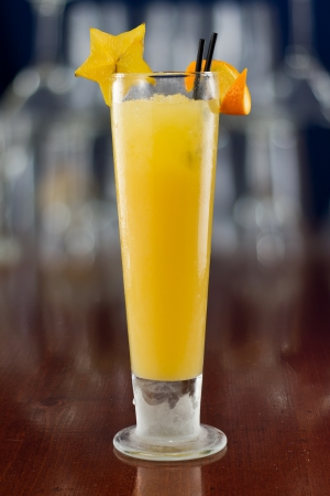 oj: fresh tall glass of yellow tropical juice decorated with a carambola slice and an orange twist Stock Photo