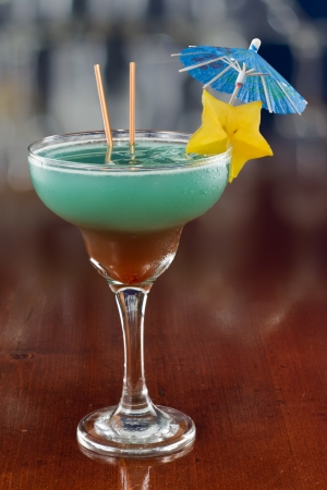 blue hawaiian cocktail served on a busy bar top garnished with a carambola slice and an umbrella photo