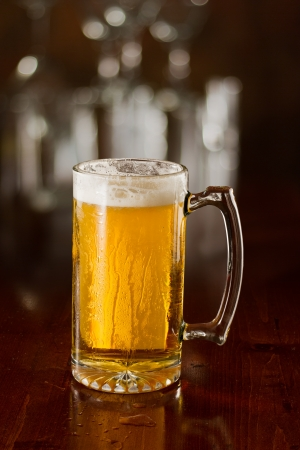 cold beer in a chilled mug served on a busy bar top Stock Photo - 18869615