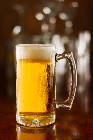 effervescence: cold beer in a chilled mug served on a busy bar top Stock Photo