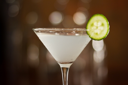 komkommer martini geserveerd op een balk boven gegarneerd met een plakje komkommer