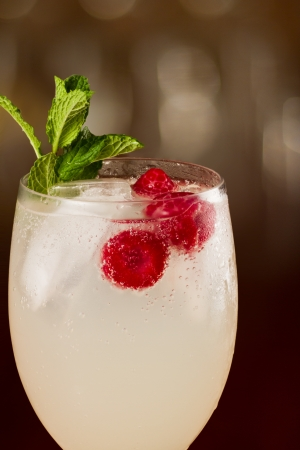 refreshing glass of water with red raspberries and green mint on a busy bar top