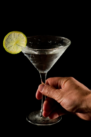 holding close: cocktail isolated on a black background garnished with a lime wheel