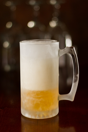 cold beer in a chilled mug served on a busy bar top Stock Photo - 18959030