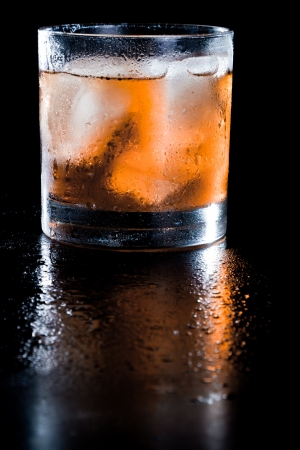 closeup of a manhattan on the rocks served on a dark bar fading in to black Banco de Imagens