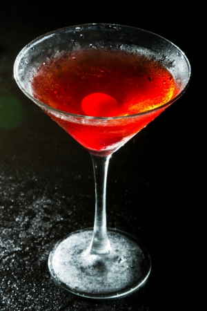 red cocktail on a dark background fading in to black garnished with a red cherry photo