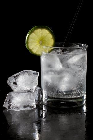 quinine: cocktail served on a dark bar top garnished with a lime wheel