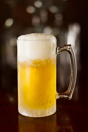 cold beer in a chilled mug served on a busy bar top photo