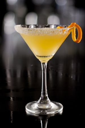 beautiful cocktail served on a dark bar garnished with an orange twist and a sugar rim