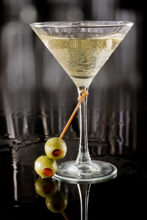 dirty vodka martini served on a dark bar garnished with large green olives