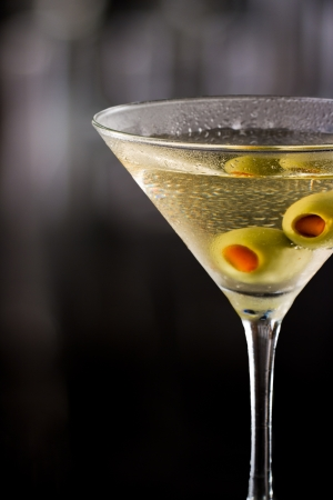 dirty vodka martini served on a dark bar garnished with large green olives photo