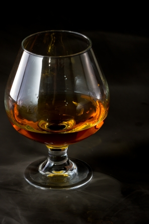 dramatic shot of a brandy snifter with whiskey served on a dark bar with fog around it