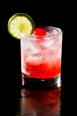 refreshing red cocktail with sparkling water and ice garnished with a lime and cherry
