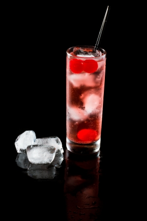 quinine: refreshing red cocktail with sparkling water and ice over a dark background
