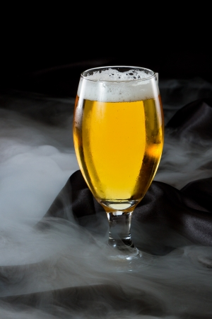 lingering: refreshing light beer in a cold glass served on a dark bar with lingering fog Stock Photo
