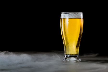 erfrischend helles Bier in einem kalten Glas serviert auf einem dunklen Balken mit Nebel