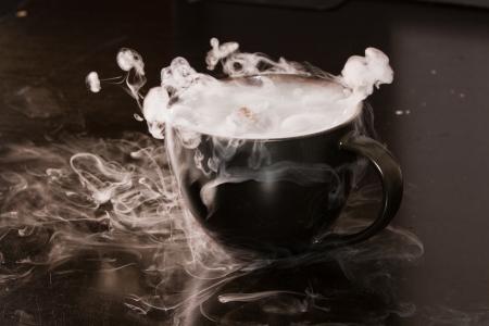 close-up van een kop met rook en bubbels in een donkere omgeving Stockfoto