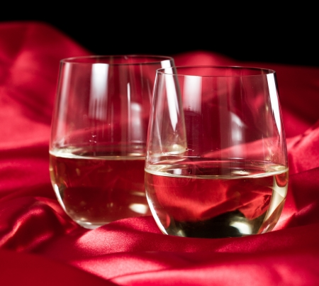 two and a half: two stemless white wine glasses served on a red silk table cloth