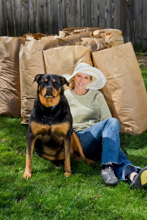 woman and her dog taking a break after cleaning up the back yard photo