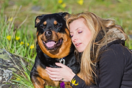 woman and her dog resting in the spring grass with yellow flowers showing affection Stok Fotoğraf