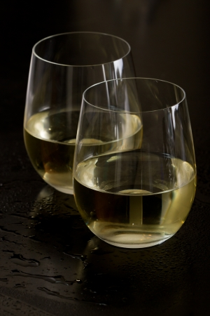 two and a half: two stemless white wine glasses on a black background Stock Photo