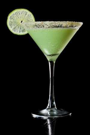 black gram: key lime martini isolated on a black background, gram cracker rim and lime wheel garnish