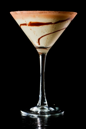 chocolate martini isolated on a black background with chocolate swirl and cocoa powder on the rim photo