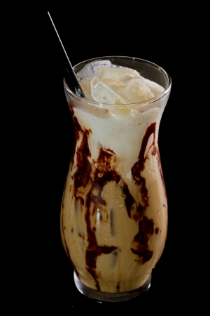 mud slide: mud slide cocktail isolated on a dark background served on the rocks with chocolate sauce in the glass