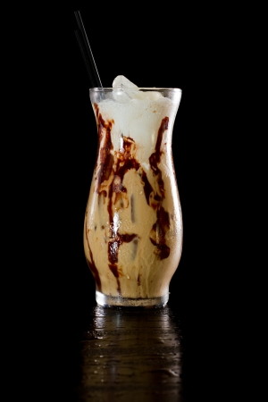 mud slide cocktail isolated on a dark background served on the rocks with chocolate sauce in the glass photo