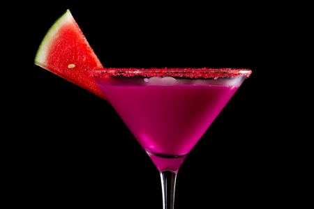 bright colorful watermelon martini isolated on a black background garnished with red sugar rim and a watermelon slice photo