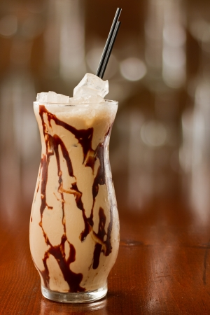 mud slide: mud slide cocktail served on a busy out of focus background with chocolate sauce in the glass