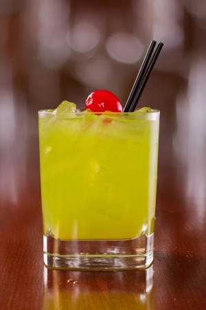 chilled out: bright green cocktail served on a busy out of focus bar with a red cherry served on the rocks