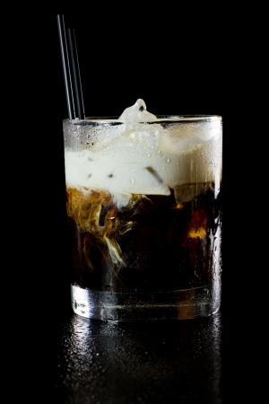 white russian cocktail isolated on a dark background served on the rocks photo