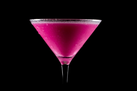 bright pink martini served on a dark bar isolated on a black background Imagens