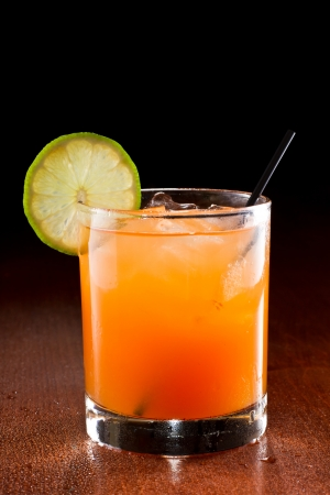 tropical juice cocktail served on a dark bar setting garnished with a lime wheel Stock Photo