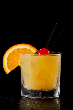 whiskey sour cocktail served on the rocks isolated on a black background garnished with an orange slice and a maraschino cherry