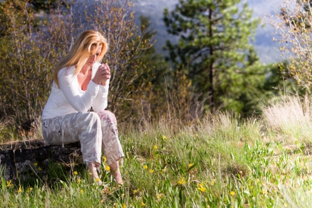 beautiful woman sitting on a rock praying with wild spring flowers around her Stock Photo