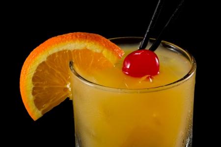 위스키 사워 칵테일, 오렌지 슬라이스와 큰 체리로 장식 된 검정색 배경에 고립 된 바위에 제공