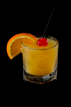 maraschino: whiskey sour cocktail served on the rocks isolated on a black background garnished with an orange slice and a maraschino cherry